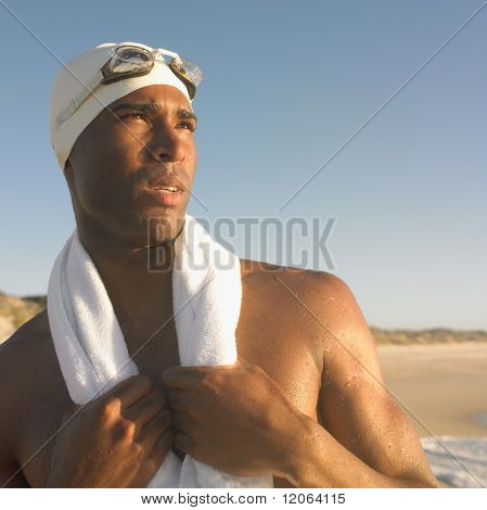 Man in swimming cap with towel around neck