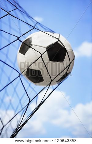 Football soccer ball in back of the net concept for goal, scoring, winning and team competition