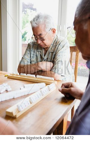 Two elderly men sitting at table playing game