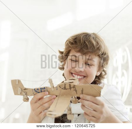 teenager with model paper ailplane in room