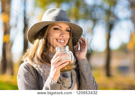 Beautiful Happy Young Woman Wearing Gray In Park Holding Glass Coffee Mug