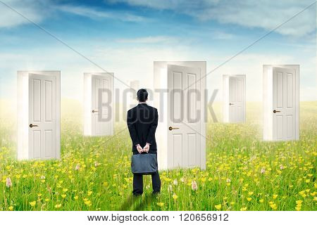 Businessman Looking At Many Doors