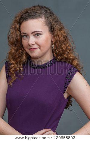 Smirking teen beauty in purple dress.