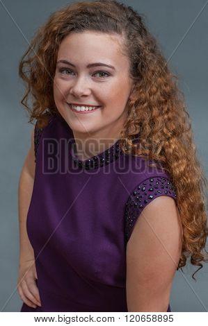 Smiling teen beauty in purple dress.
