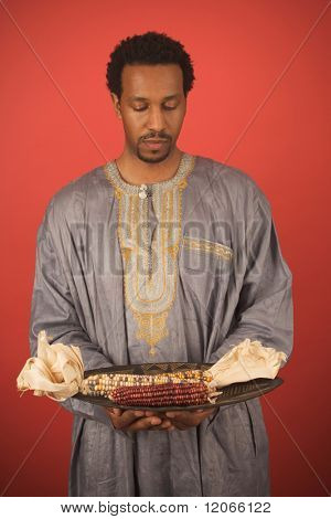 Man holding plate of corn