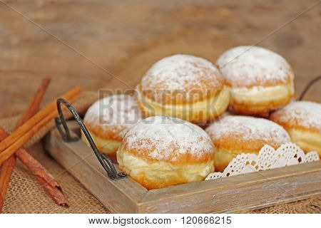 Delicious sugary donuts in wooden tray closeup