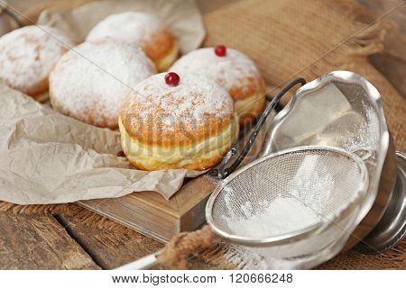Delicious sugary donuts with red currant in wooden tray with parchment closeup