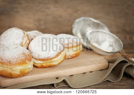 Delicious sugary donuts on wooden cutting board closeup