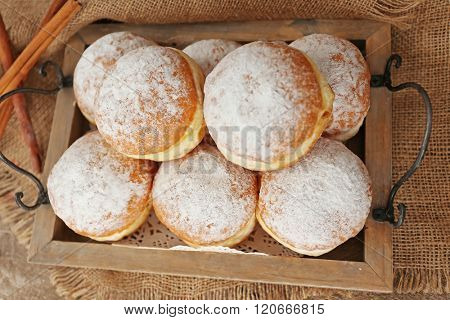 Delicious sugary donuts in wooden tray, top view