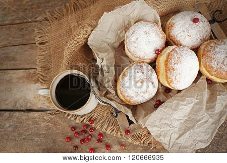 Delicious sugary donuts with red currant on wooden tray with parchment, top view