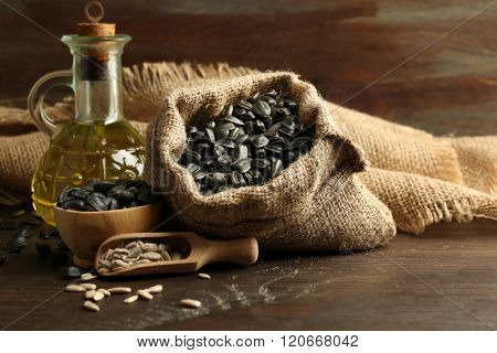 Sunflower seeds in bag and oil on wooden table background, closeup
