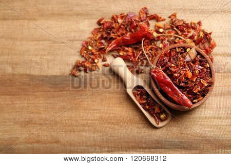 Crusher hot chili pepper on wooden table, top view