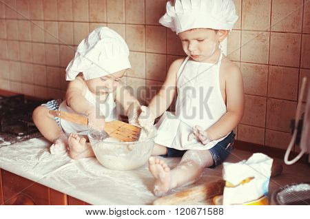 Two Little Boys Cook Play Dough On The Table In An Apron And Chef's Hat