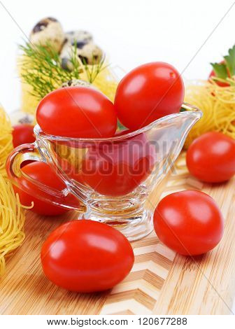 Glass Gravy Boat With Cherry Tomatoes.