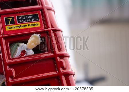 Human figure stuck in a London Bus on a white background