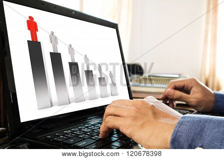 Hand using lap top, with bar graph, competition and leadership concept