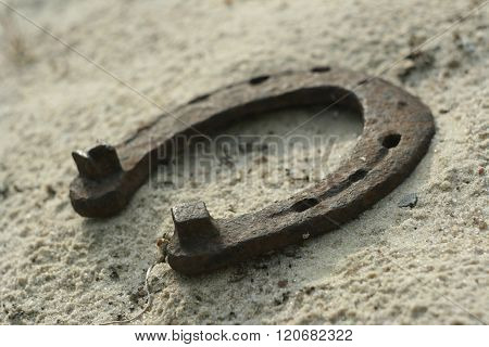 Rusty horseshoes on a sand background - rustic scene in a country style. Old iron Horseshoe - good