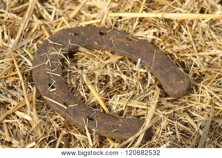 Rusty horseshoes on a straw background - rustic scene in a country style. Old iron Horseshoe - good