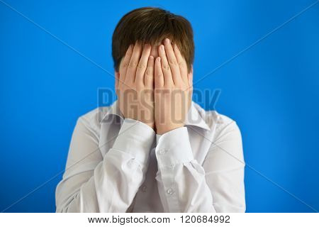 A depressed teenager boy covered his face with his hands