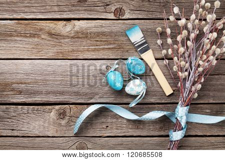 Colorful easter eggs and pussy willow on wooden table. Top view with copy space