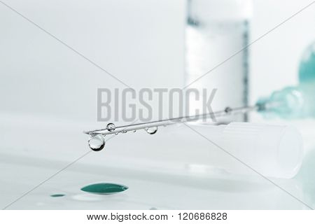 Medical syringe with injection solution drop. Shallow depth of field