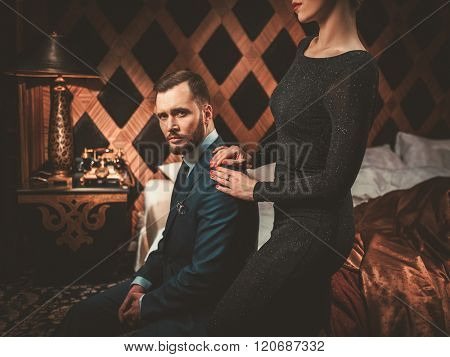 Well-dressed couple in luxury bedroom interior.