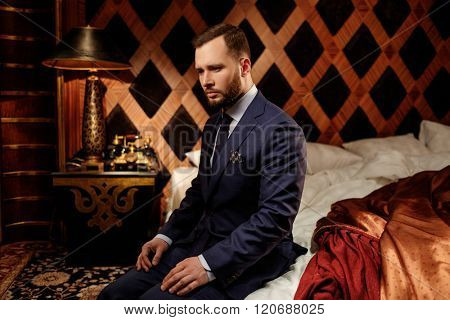 Confident well-dressed man in luxury bedroom interior.