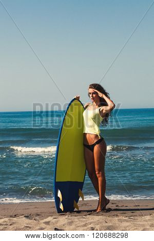 young woman prepare for surf on surfboard full body shot on sandy beach by the sea