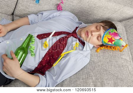 A young businessman with a drinking problem is relaxing on a sofa