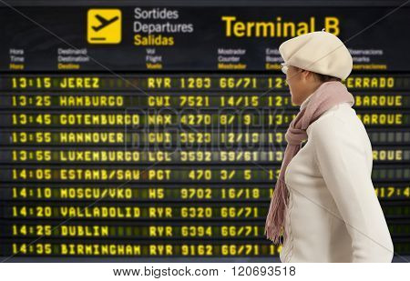 Woman looking to departure board at airport