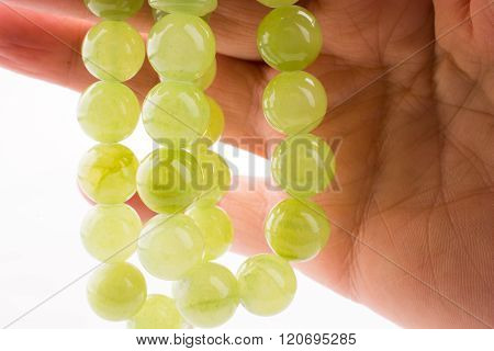Hand Holding Green Beads