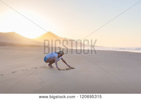 Lady drawing heart shape in sand on beach.