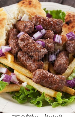 Cevapcici, bosnian minced meat kebab with onion and french fries