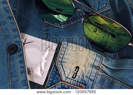 Condom and sun glasses in the vintage blue jeans pocket. Focus on the condom.