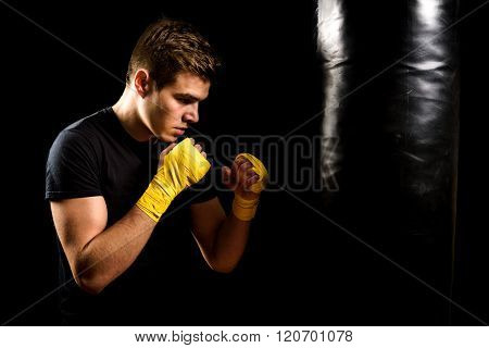 Man In Boxing Wraps Is Training And Hitting Heavy Bag.