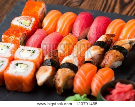 Various kinds of sushi served on black stone. Sushi Set sashimi and sushi rolls