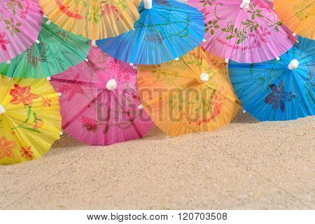 Colorful Paper Cocktail Umbrellas In Sand