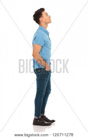 side portrait of young man in blue shirt looking up with hands in pockets while posing in isolated studio background