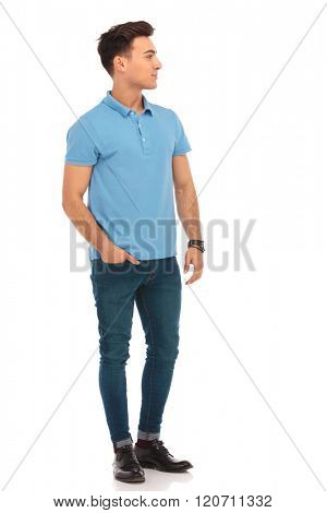 portrait of handsome man in blue shirt posing with one hand in pocket while looking away from the camera in isolated studio background