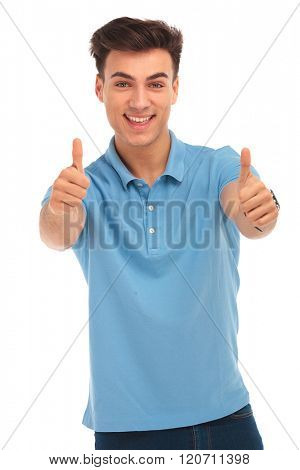 sexy young man in blue shirt smiling and showing thumbs up sign while looking at the camera in isolated studio background