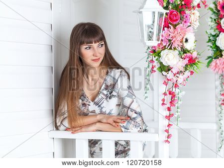 Beautiful girl on the porch with  white lantern, decorated  flowers.