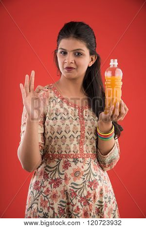 indian pretty girl with orange or mango juice bottle