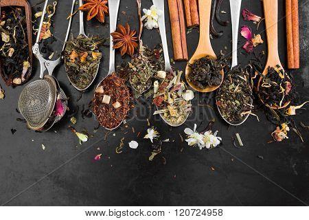 Tea In Spoon On Rustic Black Background.