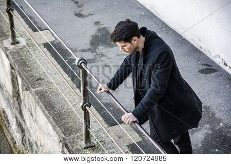 Young man in black coat looking down while leaning on railing