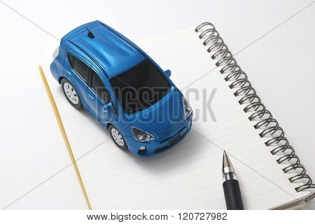Car, pen, and notebook