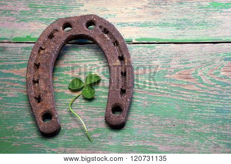 Old iron rusty metal horseshoe on weathered wood