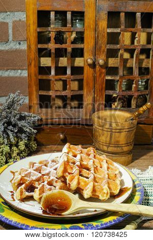Handmade fresh belgian waffles with sugar powder and caramel syrop on rural wooden background