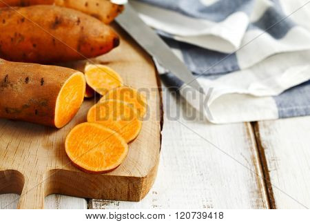 Raw sweet potatoes on wooden cooking board