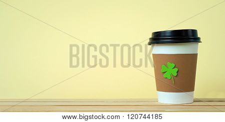 take away cup with cut and pasted green shamrock symbol
