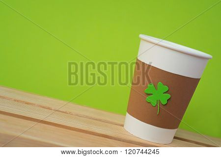 take away cup with cut and pasted green shamrock symbol on wooden desk with green wall